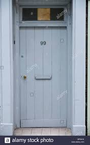 gray painted wooden front door no 99 with letterbox and glazed fanlight of house in uk
