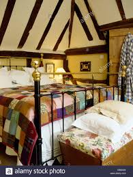 Colourful patchwork quilt on antique brass bed in cottage bedroom ... & Colourful patchwork quilt on antique brass bed in cottage bedroom with  beamed ceiling and old wooden chest Adamdwight.com