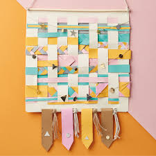 begin by making a paper loom to weave your paper through to do this take a piece of cardstock in a neutral colour we ve chosen white and using a craft