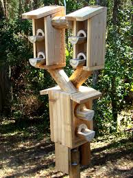 wooden bird feeders on a pole bird cages