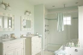 restful bathroom with sea foam blue walls painted martha stewart araucana blue framing a pair of cream faux bamboo vanities with stone counters below a pair