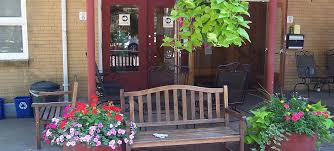 a bench with pink and red potted plants and a green leafy plant hanging from