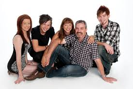 white studio family portrait colour relaxed family portrait of family of 5 with casual clothing jeans and shirts on a