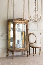 eloquence inc handsome vine vitrine with three shelves in dark gilt internal mirror shows sign of aging and gl shelves are chipped in places