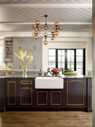 gold trim accents a black kitchen island with a white farmhouse sink and oil rubbed bronze faucet