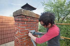 a mason repairs a chimney