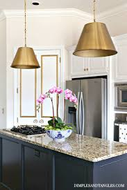 alden brass pendants white doors with gold molding black island