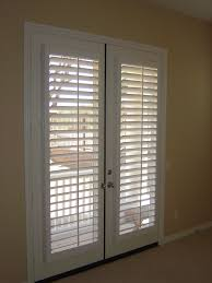 roll up roman shades on white frame patio door