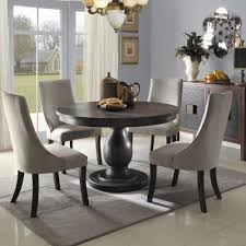 grey griffin cutback upholstered dining chair along with dark wood round dining table and grey area