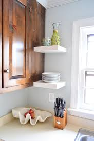 two short ikea floating shelves next to kitchen window holding stack of plates and carafe