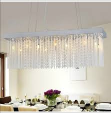 rectangle dining room crystal chandelier over dining table with flower centerpiece in crystal vase and