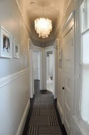 narrow small hallway painted in white walls and illuminated with capiz s chandelier