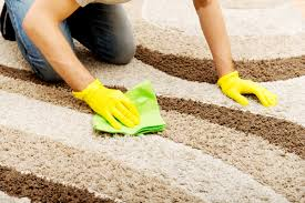 man in yellow gloves cleaning carpet