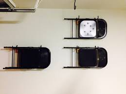simple diy wall mounted folding chair storage with hooks in the basement for saving small spaces ideas