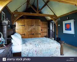 Builtin Wardrobes With Unpainted Wooden Doors In Dark Blue - Dark blue bedroom