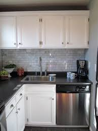 beautiful kitchen with kitchen cabinets painted behr ultra white carrara marble tile backsaplsh and black laminate countertops