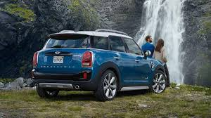 a couple with their grey mini countryman at a waterfall