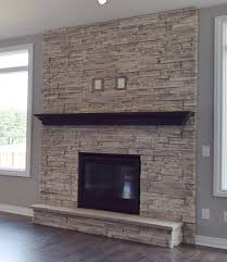 full ceiling to floor stone fireplace with finished wood mantel