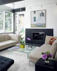 innovative lucite coffee table in living room contemporary with honed granite next to gas fireplace alongside corner gas fireplace and small den