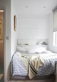 Hanway-London-Home-white-room-striped-bedspread Bed tucked away in a nook  with lots of storage underneath and above.