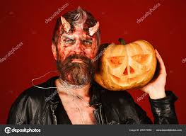 man wearing scary makeup holds pumpkin on red background party concept devil or monster with october decorations