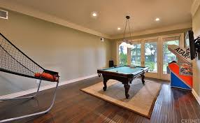 the game room features a billiards pool on top of a rug the hardwood flooring