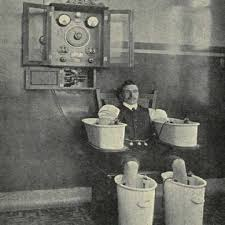 vintage photo of a man in galvanic bath seated on a chair between a pair