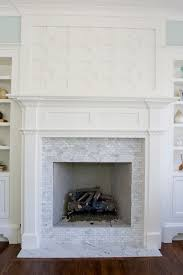 gorgeous greek key fretwork fireplace with white carrara marble tiles blue walls paint color and