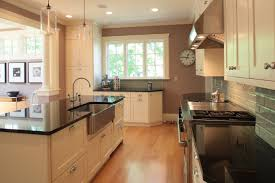great white kitchen cabinet system feat long rectangle island with sink and black granite countertops as