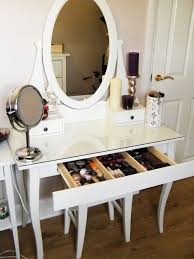 glass top vanity table with wooden base painted with white color and drawer for makeup storage built in with oval mirror beside door ideas