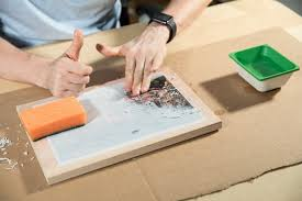 a man rubbing a wooden board to transfer photos to wood