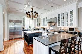 traditional kitchen with white glass faced cabinets and black quartz counter tops