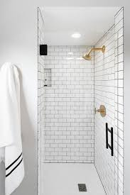 white subway shower tiles with gray grout and brushed gold shower head