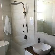 elixir square bronze shower arm with diverter in bathroom setting