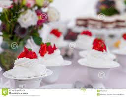 Small Wedding Cake With Strawberry On Top And Flowers In Background