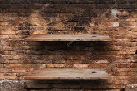 empty wood shelves on old brick wall