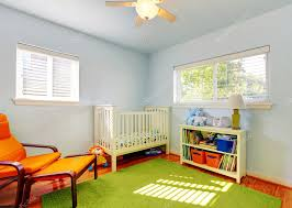 baby nursery room design with green rug blue walls and orange chair photo by iriana88w