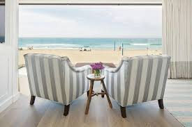 beach cottage living room features a pair of blue striped accent chairs flanking a tripod table facing a floor to ceiling window dressed in gray banded