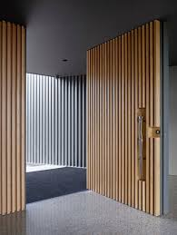 door designs. This Large Pivoting Front Door Covered In Light Wood Slats Has A Sculptural Handle Set Into The To Welcome You Home. Designs