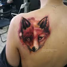 фото женской цветной татиуровки на спине лиса в стиле акварель