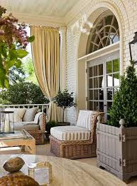 a beautiful front porch with outdoor curtains