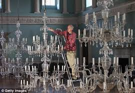 enlarge terry brotheridge works on one of the five original 18th century chandeliers in the ballroom inside