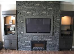 this is a gorgeous example of a dark stone facade on a fireplace surrounded ed with