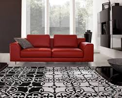 hot red leather couch and glass walls for modern living room ideas with black and white rug