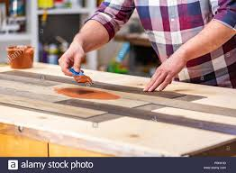 profession carpentry woodwork and people concept carpenter working with wood plank at work