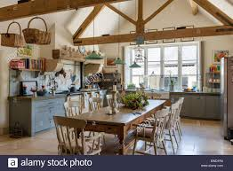 Vintage Farmhouse Table In Rustic Kitchen With Green Pendant Lights