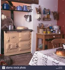 white cottage kitchens. Cream Aga Oven In White Cottage Kitchen With Earthenware Jars On Small Wooden Side-table Kitchens A