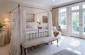 Beautiful french style bedroom with canopy bed, ottoman and french doors