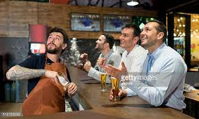 excited men watching football at the bar stock photo getty images 1