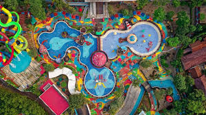 top down view of a colorful water park with umbrellas pools and rides